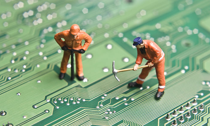 Workmen figurines on a circuit board