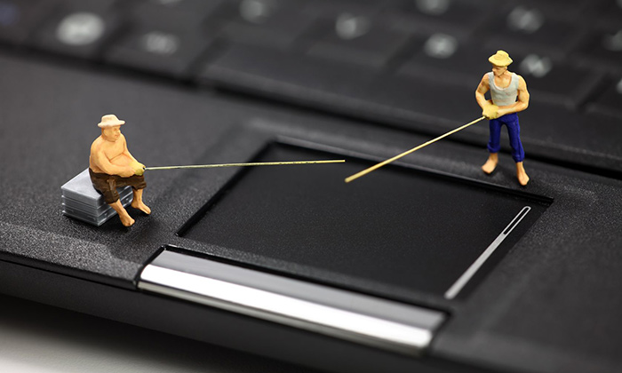 Miniature figurines on a laptop with fishing rods