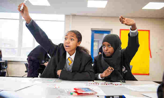 Two school students raising their hands